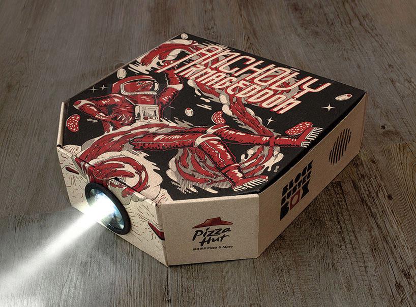 """那这到底是款怎样的包装呢?可以这么说,如果你经常吃比萨,就会发现它其实基本上跟普通用来装比萨的盒子没什么两样。只不过在设计上,这只盒子多出来两个新加的组件,并且有四种不同电影主题的插画图案。盒子的前端多了一个可以移掉的圆形开孔;盒子里面的比萨上面,还有一枚装嵌在小型底座上的塑料镜片。当盒子送至家中后,只要轻轻取下孔盖,把盒子里的镜片按进去,就可以拿起你的手机扫描一下盒子上的二维码,就可以在""""必胜客劲片精选""""中挑选一部自己喜爱的影片。赶快往后一躺,在嘴巴大快朵颐的同时,让眼睛和耳朵也"""
