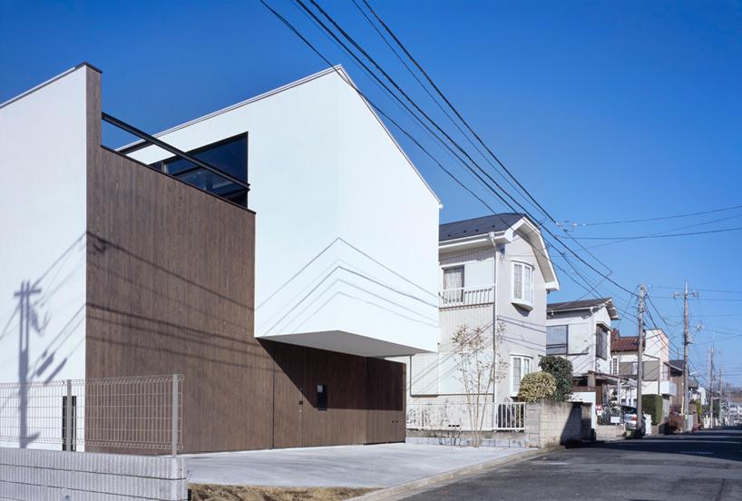 """由建筑学院翻译 图片由masao nishikawa提供 由Apollo & Associates 建筑事务所设计的""""内院式住宅""""(patio house)位于日本川崎市的一个安静的居民区。该方案以其简约的外形为特征---一个简易的白盒子从木结构中自然地伸出。建筑内部空间围绕着一个中心庭院布置。由于建筑外表面没有窗户,住宅空间给人留下了一个高度私密和封闭的印象,但是内部完全透明的玻璃墙可以最大限度地将自然光线引入房间。"""