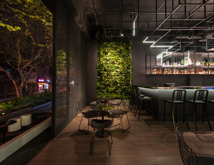 """从地板到天花板的墙壁都布满了香料植物 沙发与沙发凳采用了奢华的深蓝色,为整个空间增添了活力。不同的灯光强调出了特定的区域,从而为""""botanist""""人们的休闲与社交提供了不同的环境。桌面与吧台是由经过抛光处理的金属制作而成的,展现出了速度与活力的经典的科幻形象。与众不同的座位区则采用了透光的金属网格与嵌入的条形灯。"""