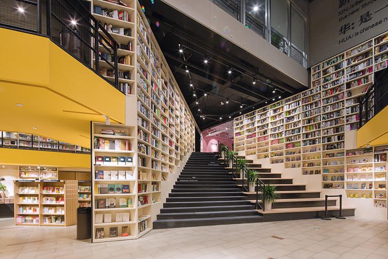 书店与图书馆综合体在安徽铜陵惊艳亮相。书店经营面积4800平方米,目前陈列图书30万册,集展演活动、艺文空间、文 创商品、图书音像经营板块为一体的体验式情景书局,店面空间设计上明亮、开阔,氛围营造上优雅、温馨,充满人文艺术气质的 氛围。    书店是设计以一个空中连廊架起了种鸽空间,用穿插的通天书架围合出一个殿堂式的购书体验中心,并用大量的明快色彩来提升整 个空间的张力,铜陵的新华书店打破了传统书架刻板的布局常规,书架在空间的游走让它充当整个室内空间的墙体和穹顶。形成了 多层次多空间随时随手可以取阅一本书